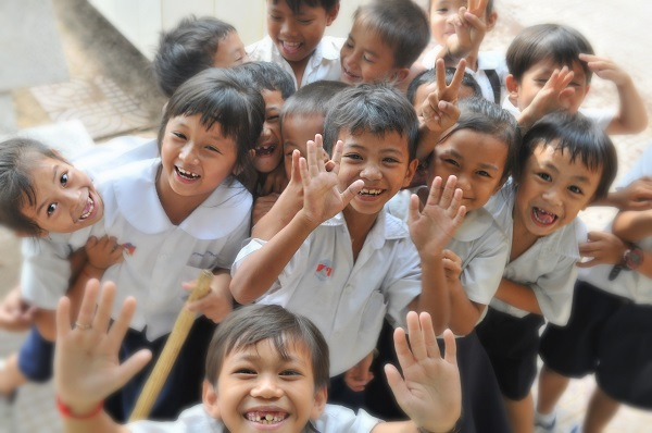 Happy School Children Playing And Looking At Camera
